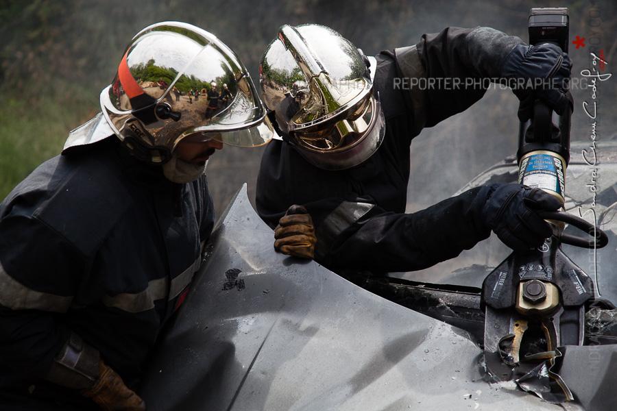 Sapeurs-pompiers de la Marne utilisant un outil de désincarcération pour accéder au moteur d'une voiture en feu [Ref:2116-13-0351]