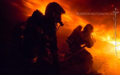Binôme de sapeurs-pompiers sous un Roll-over de flammes